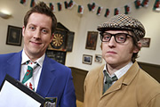 The Committee Meeting. Image shows from L to R: Mr Chairman (Chris Corcoran), Rex (Elis James). Copyright: BBC.