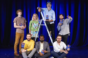 Image shows from L to R: James Acaster, Alex Horne, Sara Pascoe, Romesh Ranganathan, Sam Simmons, John Kearns, Liam Williams.