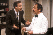 Fawlty Towers. Image shows from L to R: Basil Fawlty (John Cleese), Manuel (Andrew Sachs). Copyright: BBC.