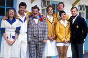 Hi-De-Hi!. Image shows from L to R: Peggy Ollerenshaw (Su Pollard), Spike Dixon (Jeffrey Holland), Ted Bovis (Paul Shane), Yvonne Stuart-Hargreaves (Diane Holland), Julian Dalrymple-Sykes (Ben Aris), Gladys Pugh (Ruth Madoc), Sqdn-Ldr Clive Dempster DFC (David Griffin). Image credit: British Broadcasting Corporation.