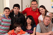In With The Flynns. Image shows from L to R: Steve (Daniel Rogers), Kevin (Alex Carter), Mikey (Lorenzo Rodriguez), Caroline (Niky Wardley), Liam (Will Mellor), Chloe (Nadine Mulkerrin), Jim (Warren Clarke). Image credit: Caryn Mandabach Productions.