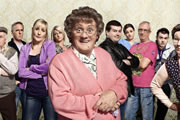 Mrs. Brown's Boys. Image shows from L to R: Grandad Brown (Dermot O'Neill), Mark Brown (Pat 'Pepsi' Shields), Cathy Brown (Jennifer Gibney), Betty Brown (Amanda Woods), Agnes Brown (Brendan O'Carroll), Dermot Brown (Paddy Houlihan), Maria Nicholson / Brown (Fiona O'Carroll), Rory Brown (Rory Cowan), Buster Brady (Danny O'Carroll), Winnie McGoogan (Eilish O'Carroll). Image credit: British Broadcasting Corporation.