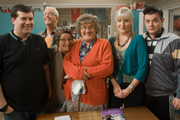 Mrs. Brown's Boys. Image shows from L to R: Dermot Brown (Paddy Houlihan), Rory Brown (Rory Cowan), Winnie McGoogan (Eilish O'Carroll), Agnes Brown (Brendan O'Carroll), Cathy Brown (Jennifer Gibney), Buster Brady (Danny O'Carroll). Image credit: British Broadcasting Corporation.