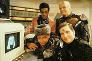 Red Dwarf. Image shows from L to R: Lister (Craig Charles), Cat (Danny John-Jules), Rimmer (Chris Barrie), Kryten (Robert Llewellyn). Image credit: BBC.