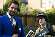 Social Club FM. Image shows from L to R: Mr Chairman (Chris Corcoran), Rex Jones (Elis James). Copyright: Zipline Creative.