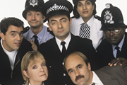 The Thin Blue Line. Image shows from L to R: D.C. Kray (Kevin Allen), P.C. Goody (James Dreyfus), Sergeant Dawkins (Serena Evans), Inspector Fowler (Rowan Atkinson), D.I. Grim (David Haig), P.C. Habib (Mina Anwar), P.C. Gladstone (Rudolph Walker). Copyright: Tiger Aspect Productions.