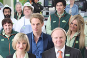 Trollied. Image shows from L to R: Ray (Adeel Akhtar), Sue (Lorraine Cheshire), Julie (Jane Horrocks), Dave (Danny Kirrane), Richard (Chris Geere), Gavin (Jason Watkins), Leighton (Joel Fry), Linda (Faye McKeever). Image credit: Roughcut Television.