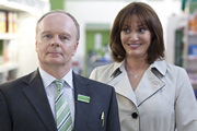 Trollied. Image shows from L to R: Gavin (Jason Watkins), Cheryl (Sarah Parish). Image credit: Roughcut Television.