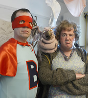 Brilliantman!. Image shows from L to R: Ian Hedge (Kevin Eldon), Mrs Wardle (Johnny Vegas). Image credit: What Larks Productions.