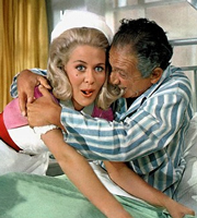 Carry On Doctor. Image shows from L to R: Nurse Parkin (Valerie Van Ost), Mr. Roper (Sidney James). Image credit: Peter Rogers Productions.