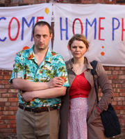Guantanamo Phil. Image shows from L to R: Phil Mill (Steve Edge), Carly (Rebekah Staton). Image credit: Busby Productions.