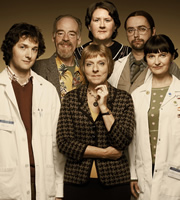 Lab Rats. Image shows from L to R: Dr Alex Beenyman (Chris Addison), Professor John Mycroft (Geoff McGivern), Dean Mieke Miedema (Selina Cadell), Minty Clapper (Helen Moon), Cara McIlvenny (Jo Enright), Brian Lalumaca (Dan Tetsell). Image credit: British Broadcasting Corporation.