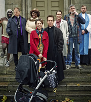 Rev. Image shows from L to R: Mick (Jimmy Akingbola), Archdeacon Robert (Simon McBurney), Adoha Onyeka (Ellen Thomas), Alex Smallbone (Olivia Colman), Rev Adam Smallbone (Tom Hollander), Ellie Pattman (Lucy Liemann), Colin Lambert (Steve Evets), Nigel McCall (Miles Jupp). Image credit: Big Talk Productions.