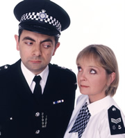 The Thin Blue Line. Image shows from L to R: Inspector Fowler (Rowan Atkinson), Sergeant Dawkins (Serena Evans). Image credit: Tiger Aspect Productions.