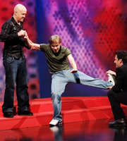 Man gets bummed by ghost whilst two people help. Image shows from L to R: Andy Parsons, Russell Howard, Adam Hills.