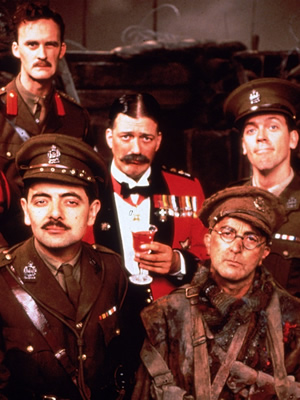 Blackadder. Image shows from L to R: Captain Kevin Darling (Tim McInnerny), Captain Edmund Blackadder (Rowan Atkinson), Lord Melchett (Stephen Fry), Baldrick (Tony Robinson), Lieutenant George Barleigh (Hugh Laurie). Image credit: British Broadcasting Corporation.
