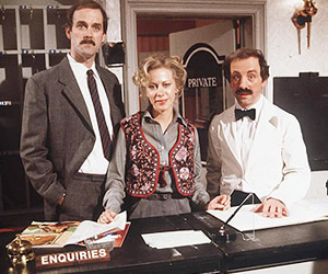 Fawlty Towers. Image shows from L to R: Basil Fawlty (John Cleese), Polly (Connie Booth), Manuel (Andrew Sachs). Image credit: British Broadcasting Corporation.