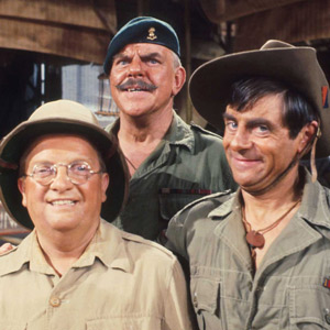 It Ain't Half Hot Mum. Image shows from L to R: Gunner 'Lofty' Sugen (Don Estelle), BSM 'Shut Up' Williams (Windsor Davies), Bombardier 'Gloria' Beaumont (Melvyn Hayes). Image credit: British Broadcasting Corporation.