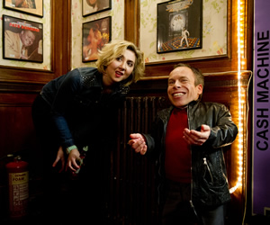 Life's Too Short. Image shows from L to R: Cheryl (Rosamund Hanson), Warwick (Warwick Davis). Copyright: BBC.