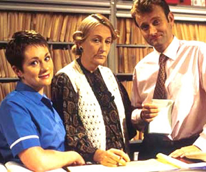 My Hero. Image shows from L to R: Janet Dawkins (Emily Joyce), Mrs Raven (Geraldine McNulty), Dr Piers Crispin (Hugh Dennis). Copyright: Big Bear Films.