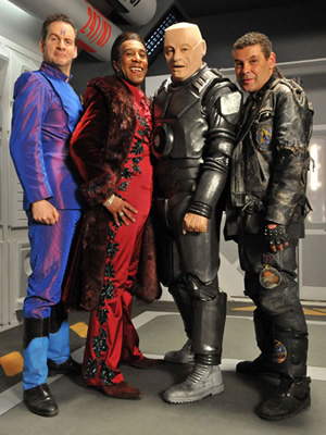 Red Dwarf. Image shows from L to R: Rimmer (Chris Barrie), Cat (Danny John-Jules), Kryten (Robert Llewellyn), Lister (Craig Charles). Image credit: UKTV.