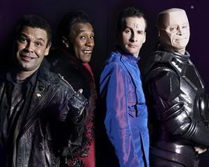 Red Dwarf. Image shows from L to R: Lister (Craig Charles), Cat (Danny John-Jules), Rimmer (Chris Barrie), Kryten (Robert Llewellyn). Image credit: UKTV.