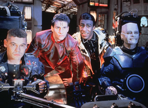 Red Dwarf. Image shows from L to R: Lister (Craig Charles), Rimmer (Chris Barrie), Cat (Danny John-Jules), Kryten (Robert Llewellyn). Copyright: Grant Naylor Productions / BBC.