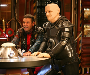 Red Dwarf. Image shows from L to R: Lister (Craig Charles), Kryten (Robert Llewellyn). Copyright: Grant Naylor Productions / BBC.