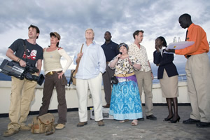 Taking The Flak. Image shows from L to R: Rory Wallace (Damian O'Hare), Jane Thomason (Doon Mackichan), David Bradburn (Martin Jarvis), Joyful Sifuri (Kobna Holdbrook-Smith), Margaret Hollis (Joanna Brookes), Harry Chambers (Bruce Mackinnon), Grace Matiko (Lydiah Gitachu). Copyright: BBC.