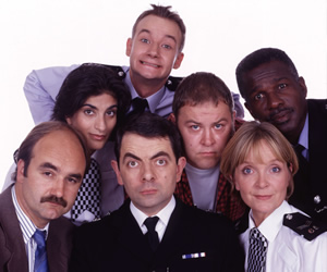 The Thin Blue Line. Image shows from L to R: D.I. Grim (David Haig), P.C. Habib (Mina Anwar), P.C. Goody (James Dreyfus), Inspector Fowler (Rowan Atkinson), D.C. Boyle (Mark Addy), Sergeant Dawkins (Serena Evans), P.C. Gladstone (Rudolph Walker). Copyright: Tiger Aspect Productions.