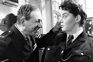 Carry On, Constable. Image shows from L to R: Sgt. Frank Wilkins (Sid James), Desk Sgt. Laura Moon (Hattie Jacques). Copyright: Peter Rogers Productions.