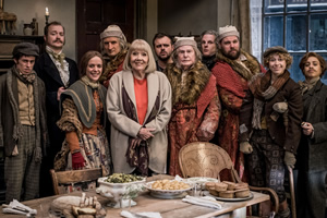 A Christmas Carol Goes Wrong. Image shows from L to R: Dennis / Bob Cratchit / Priest / Pallbearer (Jonathan Sayer), Jonathan / Marley / Topper / Businessman (Greg Tannahill), Sandra / Collector / Frances / Belle / Mrs. Cratchit / Olivia (Charlie Russell), Chris / Scrooge (Henry Shields), Aunt Diana / Narrator (Diana Rigg), Trevor (Chris Leask), Scrooge & Himself (Derek Jacobi), Max / Young Scrooge / Christmas Present / Collector / Undertaker (Dave Hearn), Robert / Bugsworth / Scrooge / Tiny Tim / Yet To Come / Pallbearer (Henry Lewis), Lucy / Tiny Tim (Ellie Morris),  Annie / Frances / Christmas Past / Businessman (Nancy Zamit). Copyright: BBC.