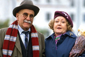 In Sickness & In Health. Image shows from L to R: Alf Garnett (Warren Mitchell), Mrs Hollingbery (Carmel McSharry). Copyright: BBC.