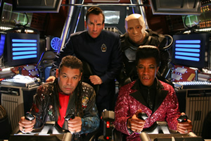 Red Dwarf. Image shows from L to R: Lister (Craig Charles), Rimmer (Chris Barrie), Kryten (Robert Llewellyn), Cat (Danny John-Jules). Copyright: UKTV.