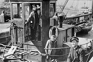 The Maggie. Image shows from L to R: The Skipper (Captain Peter MacTaggart) (Alex Mackenzie), The Engineman (McGregor) (Abe Barker), The Mate (Hamish) (James Copeland). Copyright: Studio Canal / Ealing Studios.