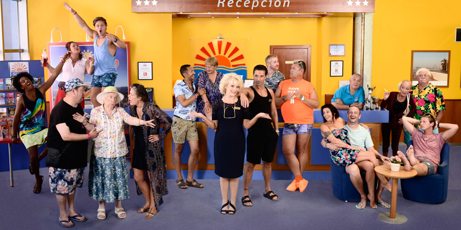 Benidorm. Image shows from L to R: Joey Ellis (Nathan Bryon), The Oracle (Johnny Vegas), Sam (Shelley Longworth), Tiger Dyke (Danny Walters), Noreen Maltby (Elsie Kelly), Pauline (Selina Griffiths), Troy (Paul Bazely), Jacqueline Stewart (Janine Duvitski), Joyce Temple Savage (Sherrie Hewson), Mateo (Jake Canuso), Liam (Adam Gillen), Kenneth (Tony Maudsley), Sheron Dawson (Julie Graham), Billy Dawson (Steve Edge), Unknown, Loretta (Kate Fitzgerald), Eddie Dawson (Bobby Knutt), Rob Dawson (Josh Bolt). Copyright: Tiger Aspect Productions.