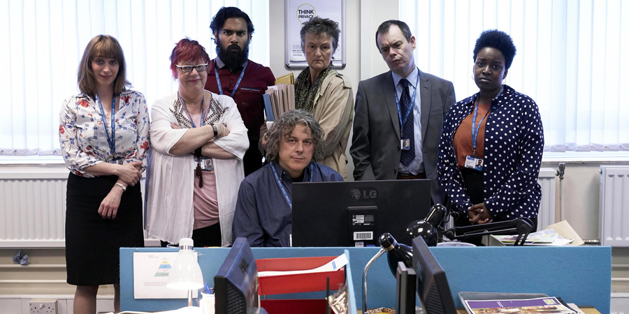 Damned. Image shows from L to R: Natalie Moore (Isy Suttie), Rose Denby (Jo Brand), Nitin (Himesh Patel), Al Kavanagh (Alan Davies), Denise Donnelly (Georgie Glen), Martin Bickerstaff (Kevin Eldon), Natalie Moore (Isy Suttie). Copyright: What Larks Productions.