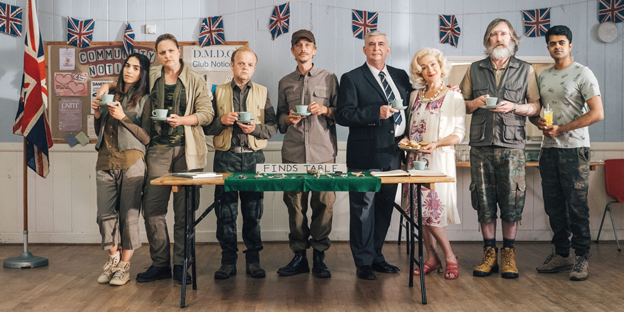 Detectorists. Image shows from L to R: Varde (Orion Ben), Louise (Laura Checkley), Lance Stater (Toby Jones), Andy Stone (Mackenzie Crook), Terry (Gerard Horan), Sheila (Sophie Thompson), Russell (Pearce Quigley), Hugh (Divian Ladwa).