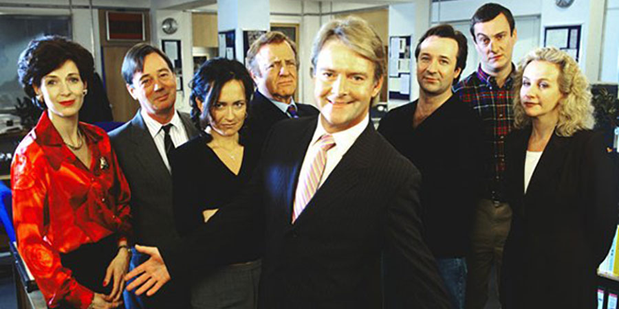 Drop The Dead Donkey. Image shows from L to R: Sally Smedley (Victoria Wicks), George Dent (Jeff Rawle), Joy Merryweather (Susannah Doyle), Henry Davenport (David Swift), Gus Hedges (Robert Duncan), Dave Charnley (Neil Pearson), Damien Day (Stephen Tompkinson), Helen Cooper (Ingrid Lacey). Copyright: Hat Trick Productions.