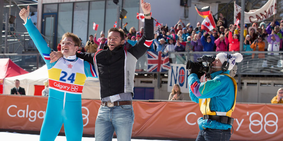 Eddie The Eagle. Image shows from L to R: Michael 'Eddie' Edwards (Taron Egerton), Bronson Peary (Hugh Jackman).