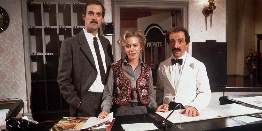 Fawlty Towers. Image shows from L to R: Basil Fawlty (John Cleese), Polly (Connie Booth), Manuel (Andrew Sachs). Copyright: BBC.