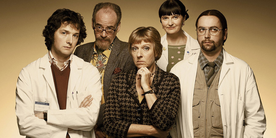 Lab Rats. Image shows from L to R: Dr Alex Beenyman (Chris Addison), Professor John Mycroft (Geoffrey McGivern), Dean Mieke Miedema (Selina Cadell), Cara McIlvenny (Jo Enright), Brian Lalumaca (Dan Tetsell). Copyright: BBC.