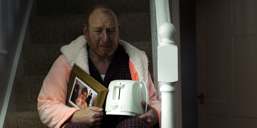 Making A Killing. Mr Loveless (Adrian Scarborough).