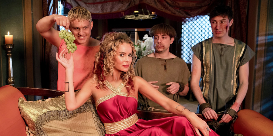 Plebs. Image shows from L to R: Jason (Jon Pointing), Rufina (Amanda Holden), Grumio (Ryan Sampson), Marcus (Tom Rosenthal). Copyright: RISE Films.