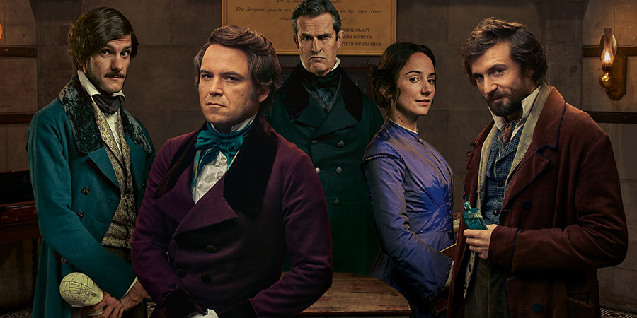 Quacks. Image shows from L to R: William (Mathew Baynton), Robert (Rory Kinnear), Dr. Hendrick (Rupert Everett), Caroline (Lydia Leonard), John (Tom Basden). Copyright: Lucky Giant.