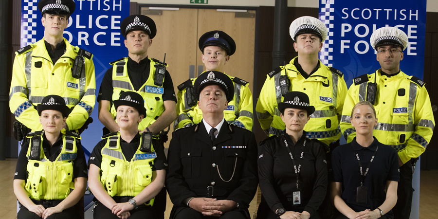 Scot Squad. Image shows from L to R: PC Jack McLaren (Jordan Young), PC Charlie McIntosh (Chris Forbes), Officer Ken Beattie (James Kirk), PC Hugh McKirdy (Graeme Stevely), PC Surjit Singh (Manjot Sumal), PC Jane Mackay (Ashley Smith), PC Sarah Fletcher (Sally Reid), Chief Commissioner Cameron Miekelson (Jack Docherty), Sergeant Karen Ann Millar (Karen Bartke), Maggie LeBeau (ML Stone). Copyright: The Comedy Unit.
