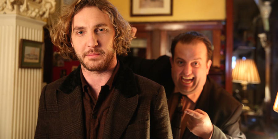 Seann Walsh In Ireland. Image shows from L to R: Robin (Seann Walsh), Hotel Receptionist (Karl Spain). Copyright: Baby Cow Productions / Sky.