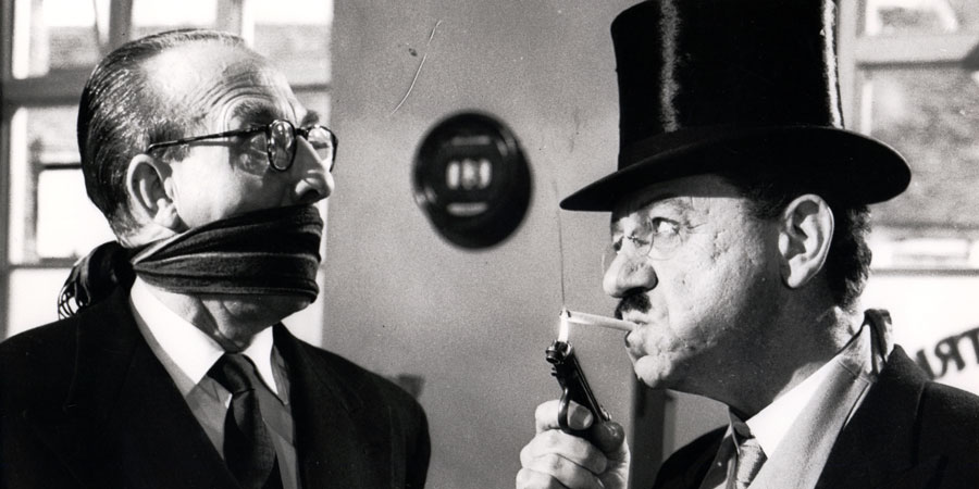 The Big Job. Image shows from L to R: Bank Cashier (Frank Forsyth), George 'The Great Brain' (Sid James). Copyright: Anglo Amalgamated.