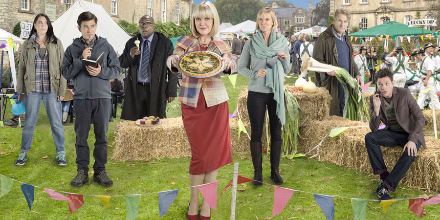 Agatha Raisin. Image shows from L to R: Gemma Simpson (Katy Wix), DC Bill Wong (Matt McCooey), DI Wilkes (Jason Barnett), Agatha Raisin (Ashley Jensen), Jo Cummings-Browne (Hermione Norris), Andy Cummings-Browne (Robert Bathurst), Roy Silver (Mathew Horne). Copyright: Mammoth Screen / Free@Last TV.