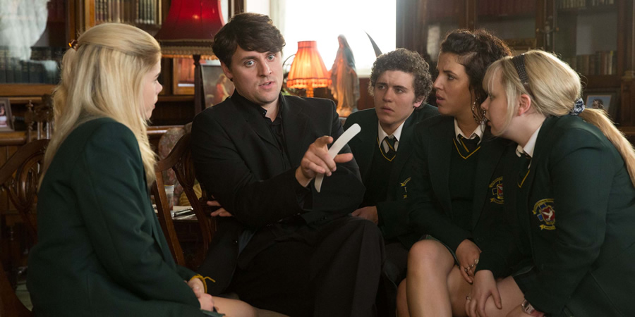 Derry Girls. Image shows from L to R: Erin Quinn (Saoirse Jackson), Father Peter (Peter Campion), James Maguire (Dylan Llewelyn), Michelle Mallon (Jamie-Lee O'Donnell), Clare Devlin (Nicola Coughlan). Copyright: Hat Trick Productions.